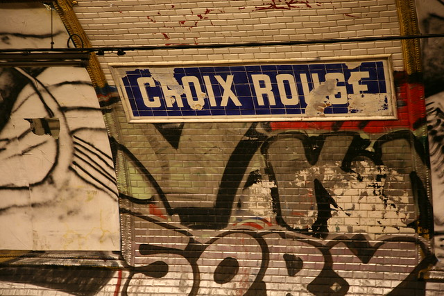 Dilapidated station name sign and graffiti in the Croix-Rouge metro station