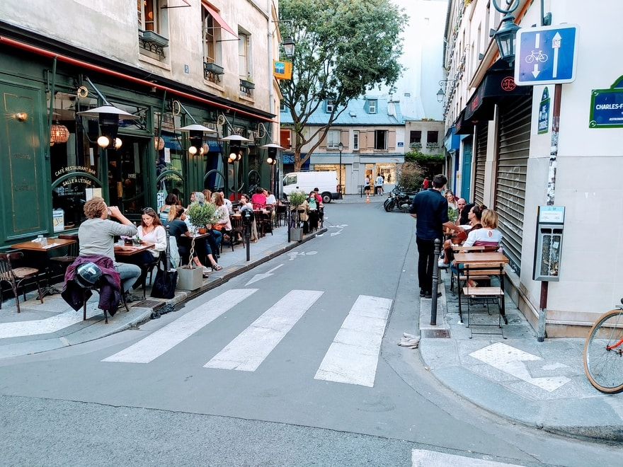 Paris street with restaurant tables occupying both pavements